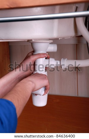 Plumber fitting the waste pipe to a kitchen sink - stock photo