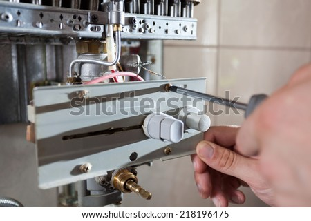 Plumber fixing a gas water heater with screwdriver - stock photo