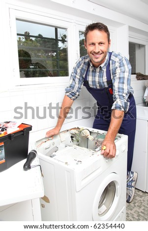 Plumber fixing broken washing machine - stock photo