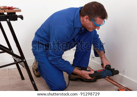 Plumber fixing copper pipe to wall - stock photo