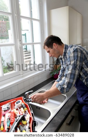 Plumber fixing domestic sink - stock photo