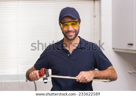 Plumber fixing pipe with wrench in the kitchen - stock photo