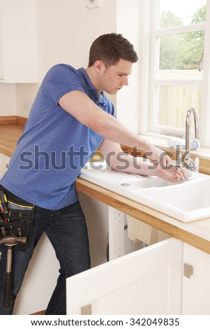 Plumber Fixing Tap With Adjustable Wrench - stock photo