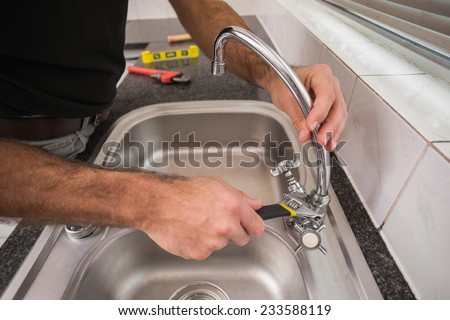 Plumber fixing the sink with wrench in the kitchen - stock photo