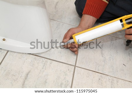 Plumber fixing toilet in a washroom with  silicone cartridge - stock photo