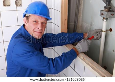 Plumber fixing water supply in bathroom - stock photo