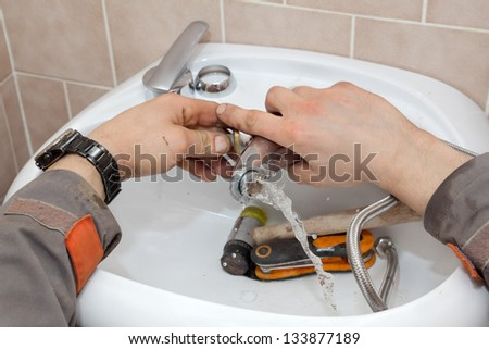 Plumber fixing water tap in a bathroom - stock photo