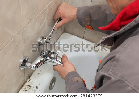 Plumber  fixing water  tap in a bathroom using spanner - stock photo