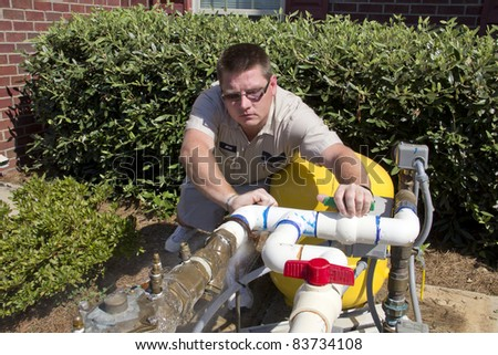 Plumber found small hole in PVC pipe that is allowing a gallon a minute to leak out on the ground, he will need to remove PVC 90 % elbow and replace it - stock photo