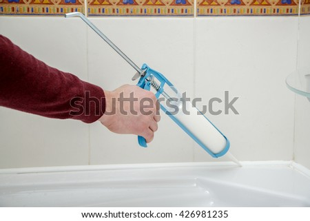 Plumber hand applying silicone sealant with caulking gun in the bathroom.