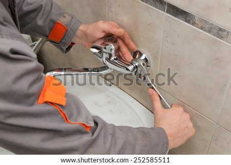 Plumber hands fixing water  tap with spanner - stock photo