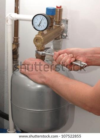 Plumber hands repairing pressure vessel with spanner - stock photo