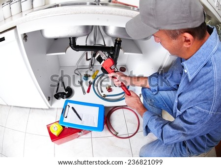 Plumber hands with a wrench. Plumbing renovation background. - stock photo