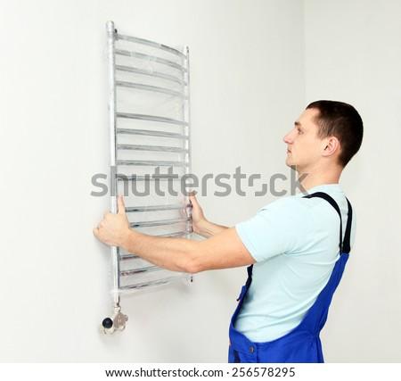 Plumber hanging towel rail - stock photo