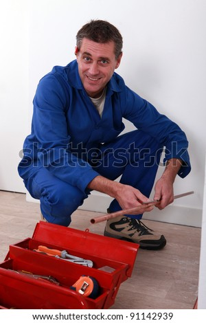 Plumber holding length of copper pipe - stock photo