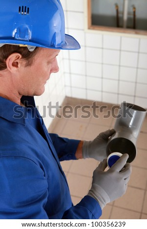 Plumber holding plastic pipe - stock photo