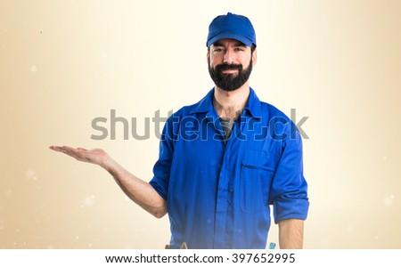 Plumber holding something over ocher background - stock photo