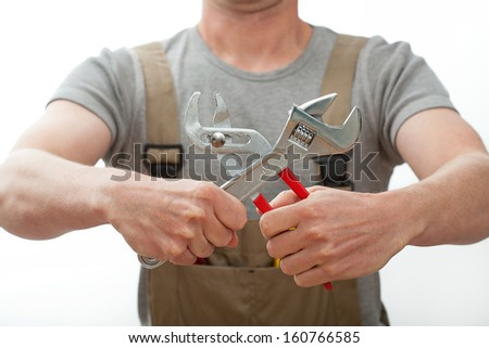 Plumber in beige overalls holding two wrenches  - stock photo