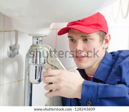 Plumber in uniform repairing old pipeline in the house. - stock photo