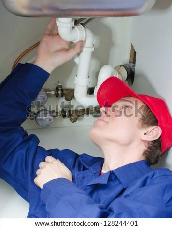 Plumber in uniform repairing pipeline in the house. - stock photo
