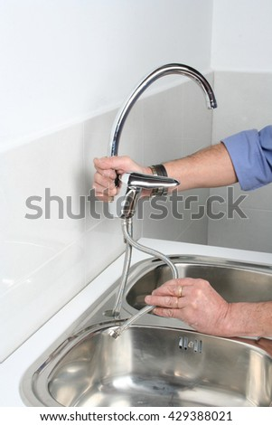 Plumber installing a faucet in a stainless steel kitchen sink