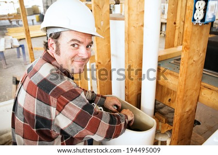Plumber installing a toilet in a home which is under construction.   - stock photo