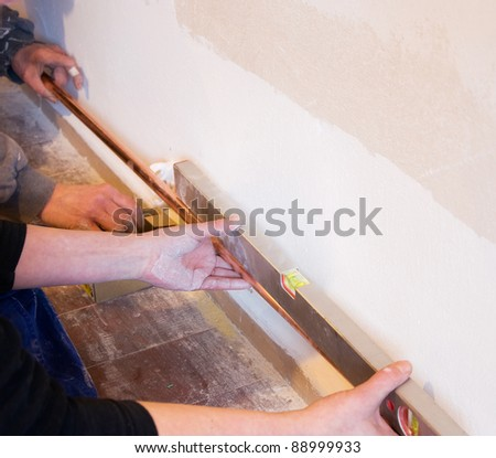 plumber installing copper pipes of a gas heating