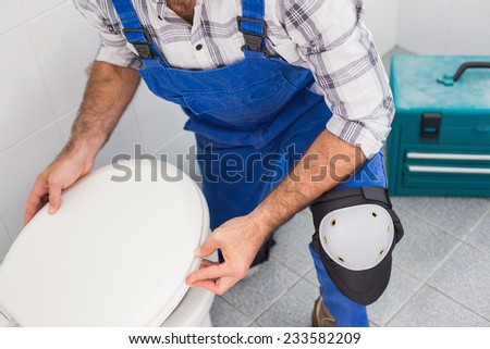 Plumber installing lid on toilet in the bathroom - stock photo