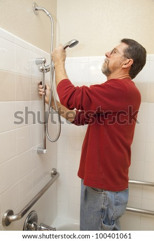 Plumber installing new shower handi-cap system to save water and cut down on water bill well making it easier for the disabled - stock photo