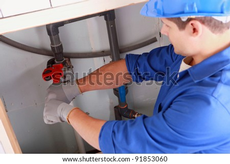 Plumber installing pipes - stock photo