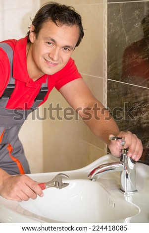 Plumber is repairing a faucet with water in the bathroom. - stock photo