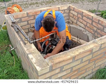Plumber is working in opened well repairing water pump. - stock photo