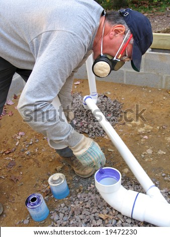 Plumber joining plastic pipes with cement for drains under a concrete slab - stock photo