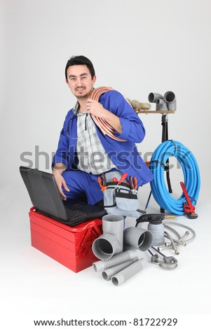 plumber kneeling with computer - stock photo