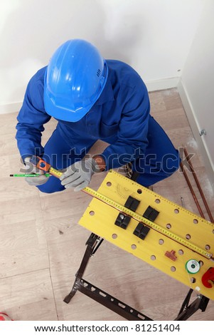 Plumber making measures on a workbench, top view - stock photo