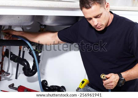 Plumber man with tools in the kitchen. Plumbing and renovation. - stock photo