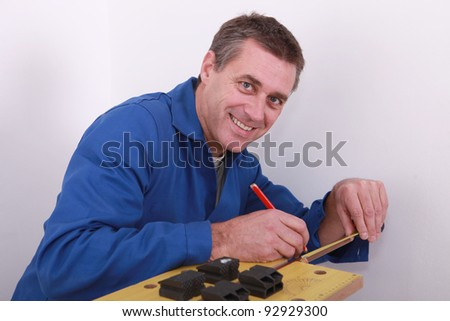 Plumber marking copper pipe - stock photo