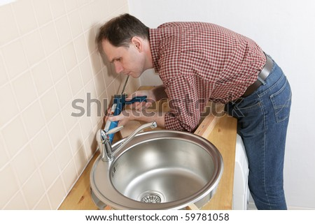 Plumber putting a silicone sealant to installing a kitchen sink - stock photo