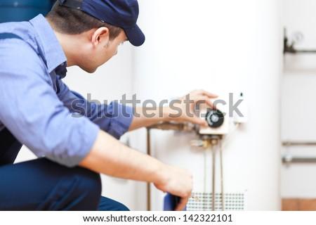 Plumber repairing an hot-water heater - stock photo