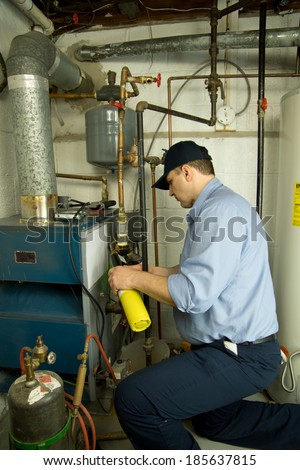 Plumber repairs furnace - stock photo