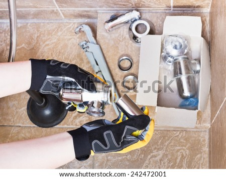 plumber replaces chrome plated trap of sink in bathroom - stock photo