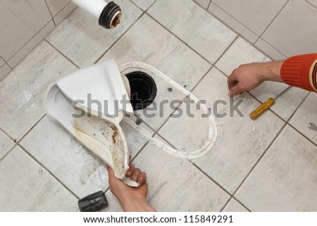 Plumber replacing broken toilet in a washroom, cutting of silicone glue - stock photo