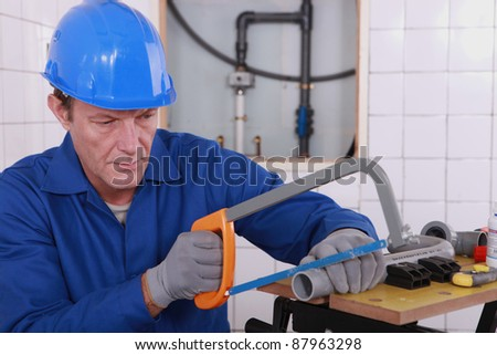 Plumber sawing plastic pipe - stock photo