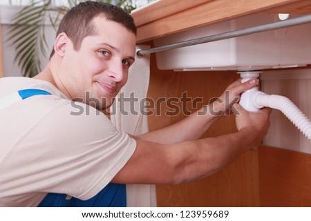 Plumber screwing siphon - stock photo