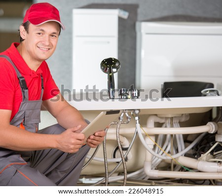 Plumber standing in front of washbasin writing on clipboard. - stock photo