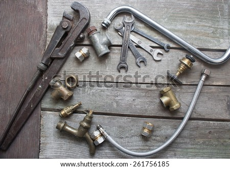 Plumber table components. Old rusty plumber spanner set, pipes, crane, tubes, wrench & water taps laying on dirty old wooden table. - stock photo