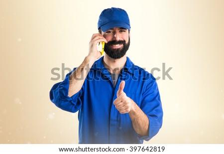 Plumber talking to mobile over ocher background - stock photo