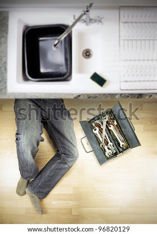 plumber under kitchen sink with toolbox full of spanners - stock photo