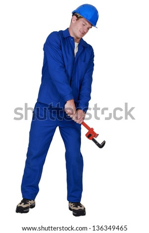 Plumber using adjustable wrench - stock photo