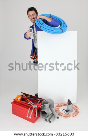 Plumber with a cellphone a board left blank for your image - stock photo